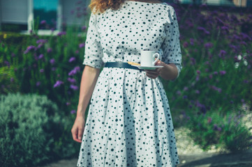 Young woman with cup of coffee in garden