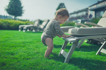 Little baby using deck chair to stand up
