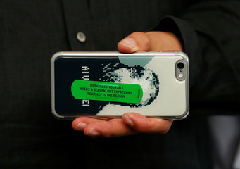 """Director Ai Weiwei holds his mobile phone as he poses during a photocall for the movie """"Human Flow"""" at the 74th Venice Film Festival in Venice"""
