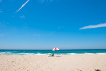 beach holiday with white-red strip umbrella and someone who taking sunbath on the beach chair