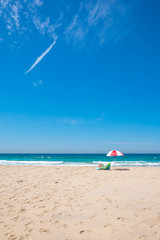 white-red strip umbrella and someone who taking sunbath on the beach chair on the beach front with the blue sky