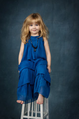 adorable little girl with her hair in a blue dress sitting on a high stool in the Studio
