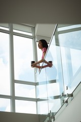Woman leaning over balcony while holding coffee mug