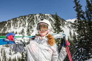 Young woman ski goggles and a helmet holding ski in the mountains.