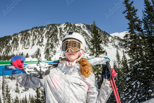 af86badd3a6 Young woman ski goggles and a helmet holding ski in the mountains ...