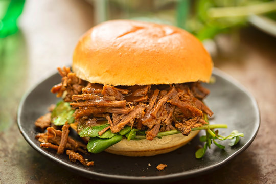 Sweet bun barbecue beef brisket with watercress leaves. Whisky barrel chip smoked British beef brisket with smoky barbecue sauce