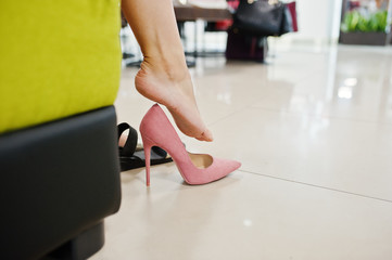 Close-up photo of woman's legs in bright colorful high heels.