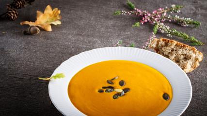 Autumn background scene of pumpkin soup with pumpkin seeds.