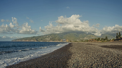 A rocky beach and big green hills under the clouds, Le Port, Reunion