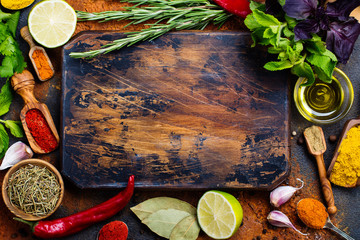 Selection of herbs and spices on grunge vintage stone table. Cooking or healthy eating concept. Copy space. Flat lay