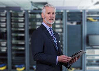 Senior businessman in network server room