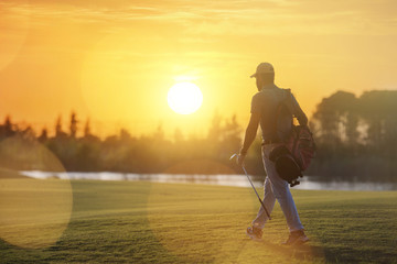 handsome middle eastern golfer carrying bag and walking to next hole
