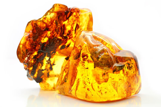 Natural amber. Two extraordinarily beautiful pieces of transparent yellow amber with inclusions on a white background with a bokeh effect. A natural mineral for jewelry. Color texture of sunstone