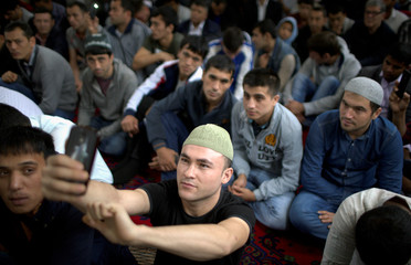 Man takes a selfie as people attend prayers for the Muslim holiday of Eid Al-Adha at a mosque in Gdansk