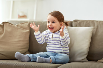 happy smiling baby girl sitting on sofa at home
