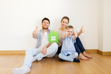 family with green house showing thumbs up at home