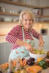Senior woman mixing vegetables salad in kitchen