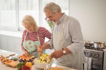 Smiling senior couple preparing salad in kitchen