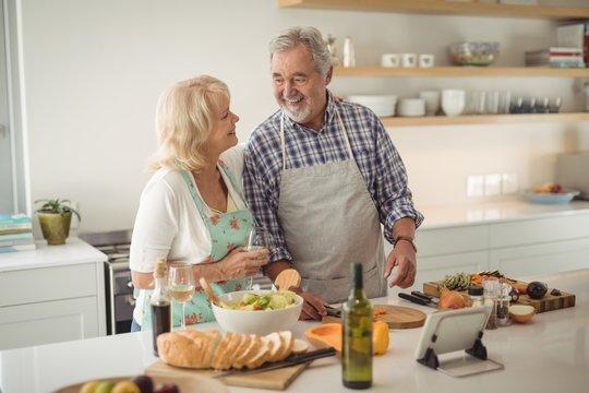 Senior couple preparing meal in kitchen