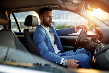 Attractive man in business suit driving car.