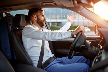 traffic jam - stressed businessman driving car.