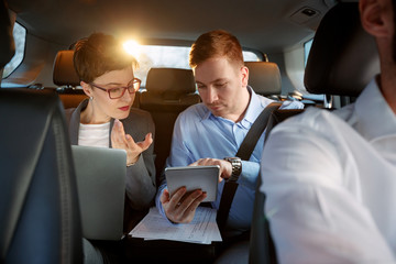 businesspeople with computer and tablet in car on trip.