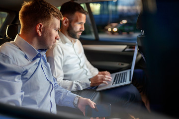 Businesspeople work on late night in back seat of car.