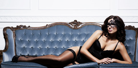 Sexy, gorgeous, young woman in erotic lingerie posing on a blue sofa in vintage interior.