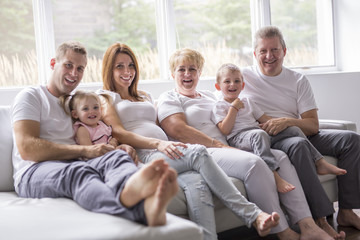 family, happiness, generation and people concept on the sofa