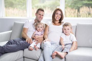Beautiful family portrait sitting in the living room at home