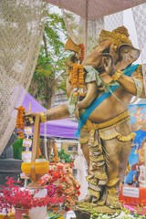 The old Ganesha statue is set for people to worship in Wat Arun, Bangkok, Thailand. Chains of Thai Paper Money Hung offering in Buddhist Temple for Good Luck