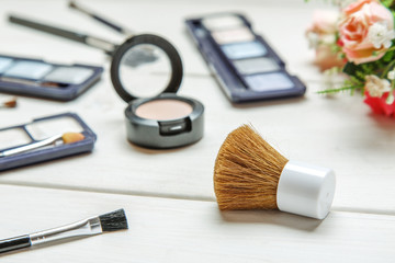 Big cosmetic brush among makeup items on a white wooden table