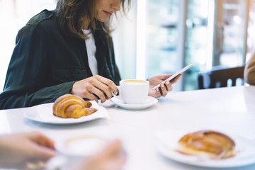 Fotomurales - Young woman holding in female hands mobile phone and drink hot aroma coffee or tea in breakfast time, hipster traveler girl in the morning using smartphone; holiday relax white cafe