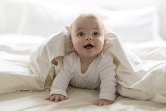 Cute happy 7 month baby girl in diaper lying and playing