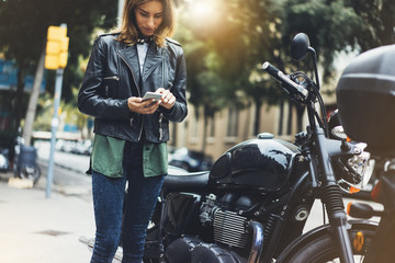 Girl in leather jacket holding smart phone on background motorcycle in sun flare city, hipster using in hands and texting mobile, motorbike street lifestyle, tourist planing route in summer Wall mural