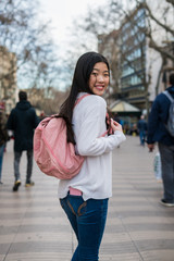 Happy young chinese woman smiling with a bag in Plaza Catalunya, Spain, Barcelona