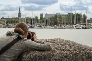 Une femme photographe vue de dos qui prend des photos de bateaux dans un port de plaisance