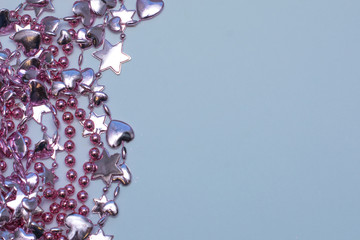Christmas card. Christmas pink beads on a blue background. Decorations for new year.Beads, Star, Heart. mock up sample
