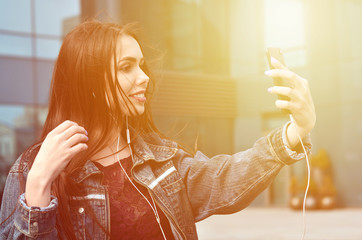 Young girl doing selfie on the background of an office building