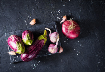 Some eggplants, garlic and red onion on a black board and background