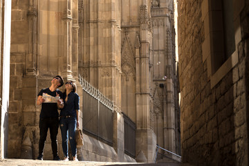 Young tourist couple walking in Barcelona city with a map in hand