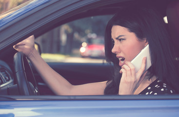 Side profile angry driver woman talking on mobile phone.