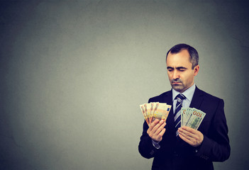 Thoughtful business man looking at euro and dollar cash banknotes