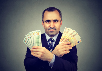 Mature business man with euro and dollar cash banknotes