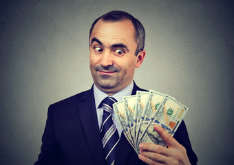 Funny sly business man holding looking at money dollar banknotes