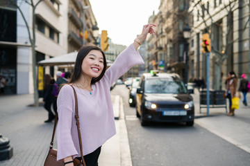 Young chinese woman asking for a cab in barcelona, raising her arm