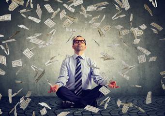Mature business man meditating under money rain