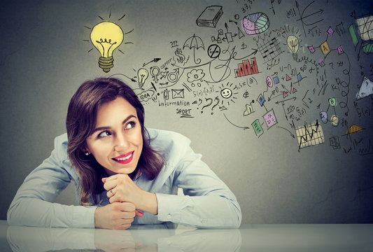 Thinking happy young business woman sitting at desk planning