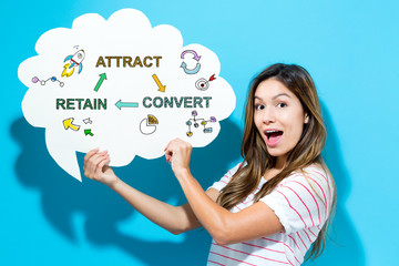 Attract Convert Retain text with young woman holding a speech bubble on a blue background