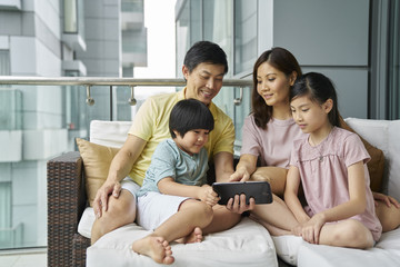 Family bonding on the balcony over an electronic tablet